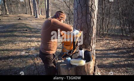 Theme hiking and travel. A Caucasian tourist man unpacks an orange backpack, takes out his things and puts them on a stump in the forest. Equipment an - Stock Photo