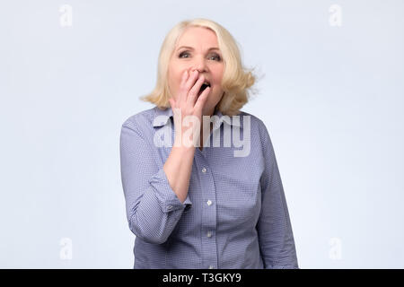Blonde woman shocked covering mouth with hands. - Stock Photo