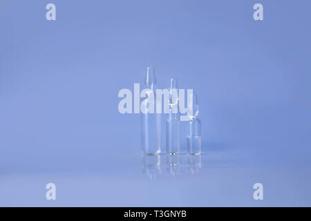 Raw of ampoules with liquid for injection. Break-seal glass ampules with medicine liquid on blue - Stock Photo