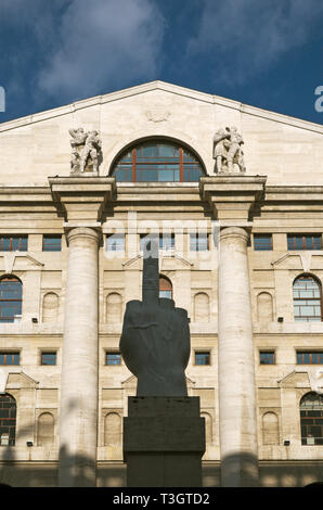 ´The Finger´ sculpture by Maurizio Cattelan, facing Palazzo Mezzanotte (Stock Exchange Building) in Piazza degli Affari, Milan, Italy - Stock Photo