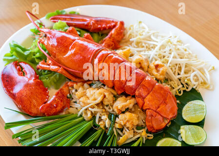 Lobster Pad thai, stir fried Thai rice noodle pasta with whole lobster and lobster meat. - Stock Photo
