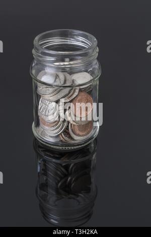 Glass jar containing UK coins - as metaphor for personal savings, rainy day saving, pensions savings pot. - Stock Photo