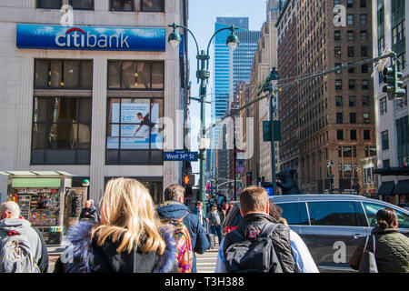 New York, NY - April 3, 2019: View up seventh avenue at the 34th street intersection in Manhattan, New York City with crowds of people and street sign - Stock Photo