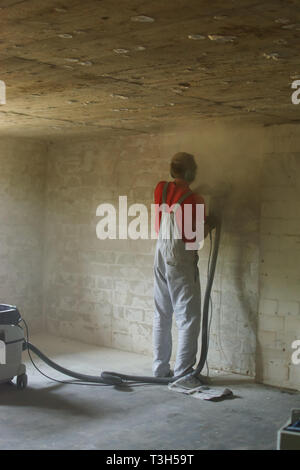 young man grinds wall in basement cellar for renovate - Stock Photo