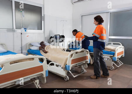 Medical Centre intensive care unit with beds and patient on oxygen showing portable defibrillator and ventilator equipment plus ward doctor and nurse