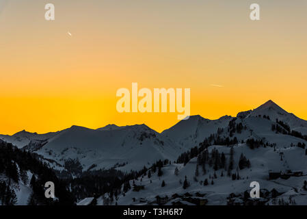 Yellow skies at sunset over the mountains in Obertauern, Austria - Stock Photo