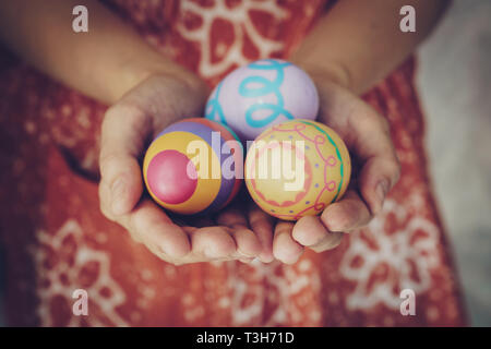 Women hands holding easter eggs painted color on hand - Stock Photo