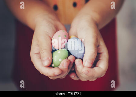 Little girl hands holding easter eggs painted color on hand - Stock Photo