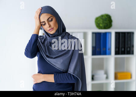 Muslim woman having a headache - Stock Photo