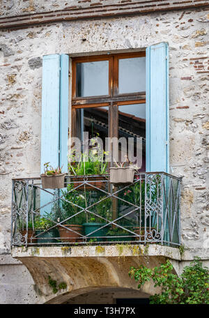 A balcony decorated with flower pots in a village in France, Europe - Stock Photo