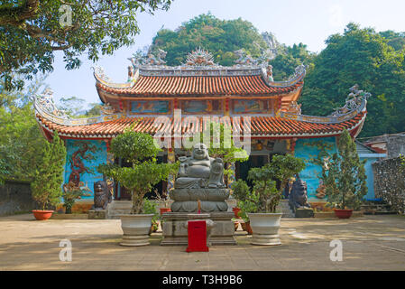 Sculpture of the happy Buddha on the background of the old Tam Thai pagoda. Marble Mountains in the vicinity of Da Nang. Vietnam - Stock Photo