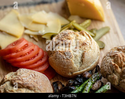 Baked portobello mushroom burger with addition fresh lettuce, tomato, asparagus and fresh spinach leaves - Stock Photo