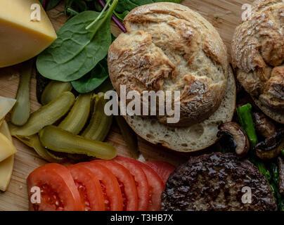 Baked portobello mushroom burger with addition fresh lettuce, tomato, asparagus and fresh spinach leaves - Stock Photo