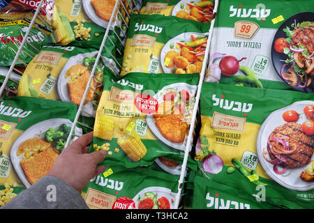 Freezer filled with packaged frozen food in a Victory supermarket. - Stock Photo