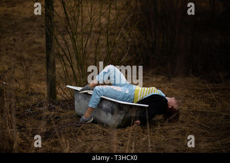 Young woman in clothes is taking an empty old bath in the middle of a forest - Stock Photo