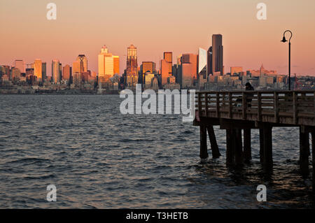 WA16104-00...WASHINGTON - Setting sun glowing on the downtown Seattle highrises at dusk from Seacrest Park on the shores of Elliott Bay. - Stock Photo