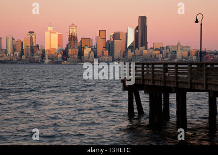 WA16105-00...WASHINGTON - Setting sun creatomg a glow on the downtown Seattle highrises at dusk from Seacrest Park on the shores of Elliott Bay. - Stock Photo