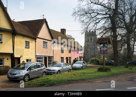 View of cottages and Church Of St John The Baptist beside the small village green in Stoke by Clare, Suffolk, England, UK - Stock Photo
