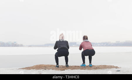 Two slim women standing on the snowy beach and doing squats