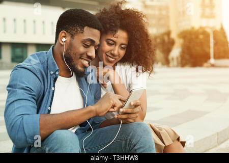 Couple listening to music with earbuds from smartphone - Stock Photo