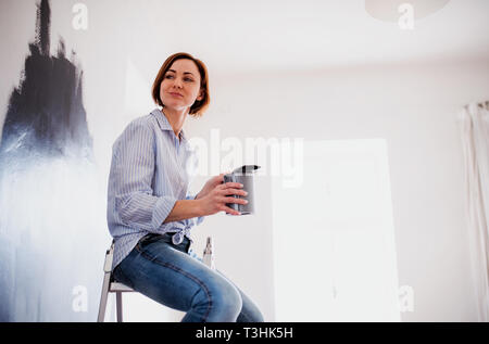 A portrait of young woman painting wall black. A startup of small business. - Stock Photo