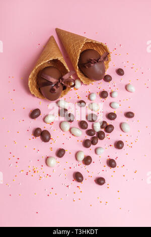 Chocolate brown eggs with ribbons in waffle's cup on pink background. Easter traditional celebtation in Europe with gifts. - Stock Photo