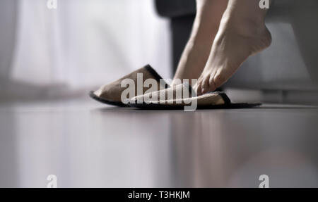 woman wearing slippers getting up out of bed - Stock Photo