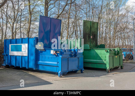 two large garbage compactors standing on a hospital site - Stock Photo