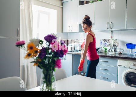 Young housewife washing floor with mop in modern kitchen decorated with flowers. Household chores - Stock Photo