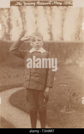 Vintage Photographic Postcard Showing a Young Boy Standing To Attention and Saluting at The Time of The First World War. 'The Young Recruit, May 1915' - Stock Photo