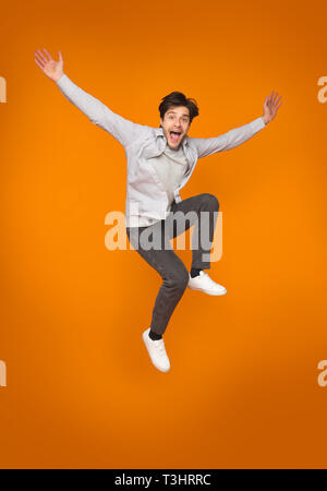 Funny man jumping with raised arms over orange background - Stock Photo