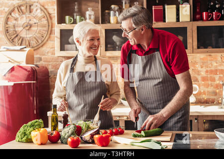 Happy senior couple cooking together on kitchen - Stock Photo