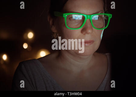Low key portrait of busy woman working on laptop computer at night from her home office - Stock Photo
