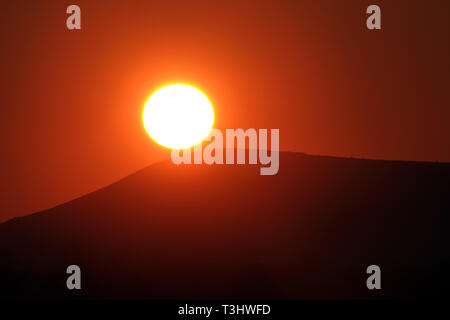 Sun setting behind the Iron Age fort on top of Mount Caburn in the South Downs national park, East Sussex. UK - Stock Photo