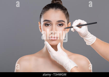 Female face with doctor's hands with pencil - Stock Photo