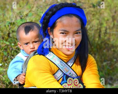 Young Hani woman (Chinese ethnic minority) carries her baby boy on her back in a baby sling with ethnic design. - Stock Photo
