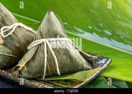 Close up, copy space, famous chinese food in dragon boat (duan wu) festival, steamed rice dumplings pyramidal shaped wrapped by bamboo leaves made by  - Stock Photo