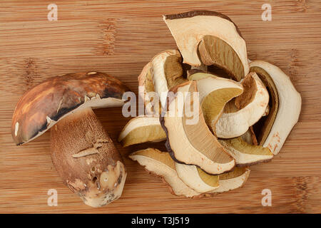 Wild mushrooms arrangement, fresh and dry porcini on wooden background with copy space - Stock Photo