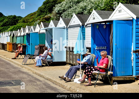 People relax and enjoy the sunshine in front of the beach huts along West Undercliff Promenade on the seafront at Bournemouth, Dorset, England, UK - Stock Photo