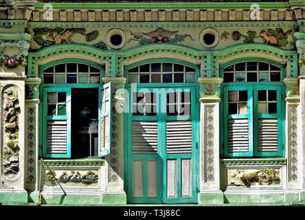 Front view of colourful exterior of a traditional Straits Chinese or Peranakan shop house with antique green wooden shutters in Geylang Singapore - Stock Photo