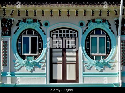 Front view of traditional vintage Peranakan or Straits Chinese Singapore shop house with ornate exterior, unique oval windows in historic Little India - Stock Photo