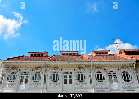 Front view of traditional Peranakan or Straits Chinese Singapore shop house exterior with unique oval windows  in historic Little India - Stock Photo