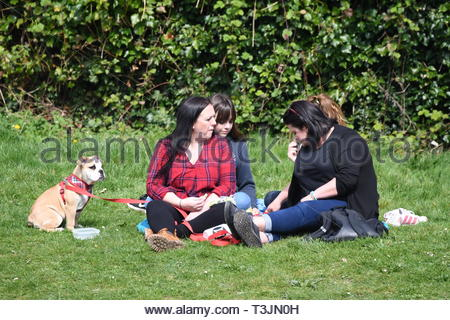 Arundel, West Sussex, UK. Wednesday 10th April 2019. People sitting on grass by a lake on a partly cloudy but bright and cool morning in Arundel, near the South Coast. Credit: Geoff Smith/Alamy Live News - Stock Photo