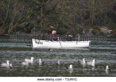 Arundel, West Sussex, UK. Wednesday 10th April 2019. People in a rowing boat on Swanbourne Lake on a partly cloudy but bright and cool morning in Arundel, near the South Coast. Credit: Geoff Smith/Alamy Live News - Stock Photo