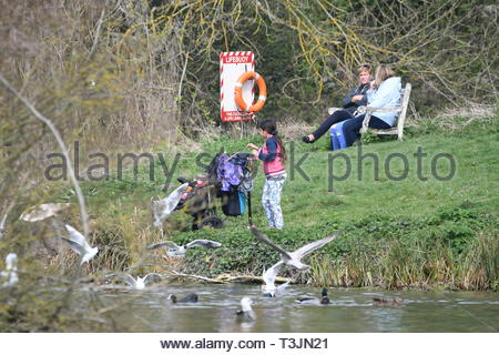 Arundel, West Sussex, UK. Wednesday 10th April 2019. Children feeding ducks at Swanbourne Lake on a partly cloudy but bright and cool morning in Arundel, near the South Coast. Credit: Geoff Smith/Alamy Live News - Stock Photo