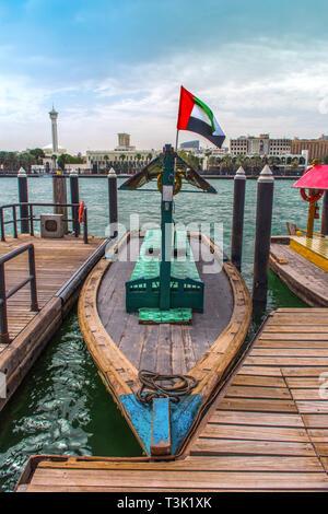 Traditional Boat Ride Abra Dubai Deira Creek, Place to visit in Dubai Blue Lake with flying UAE Flag - Stock Photo
