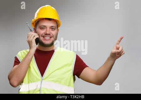 Photo of cheerful foreman in yellow helmet talking on walkie-talkie pointing his finger up - Stock Photo