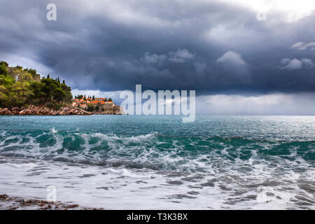 Splashes of fresh foaming, bubbling sea water, stormy sky, dark clouds, white crest of waves, Stony coast of Montenegro. Adriatic sea.