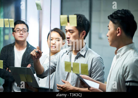 young asian entrepreneur of small company drawing a diagram on glass during team meeting discussing and analyzing business situation in office. - Stock Photo