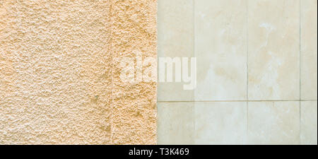 Two colored wall background consists of marble tile wall and rough textured plaster wall surface - Stock Photo